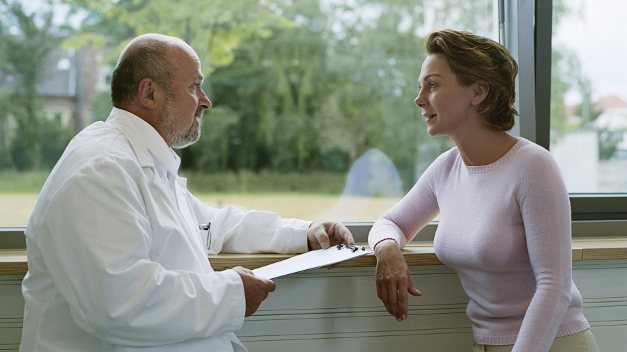 Male doctor talking to female patient by a window.