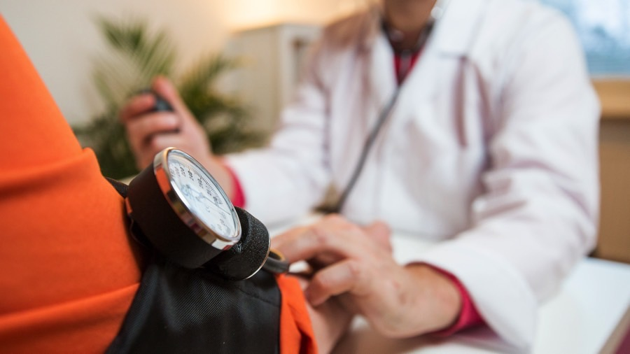 Physician checking patient blood pressure.