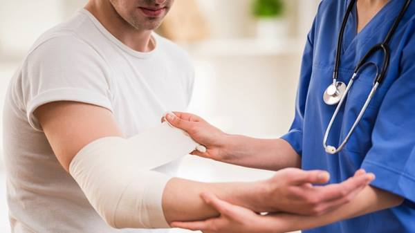 Physician wrapping a wound.