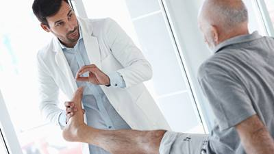 Doctor examines male patients ankle