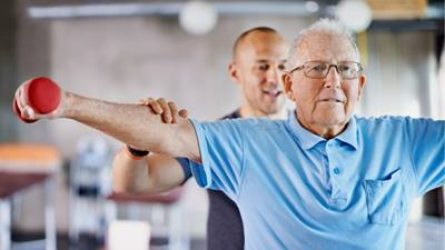 Elderly man working out with a personal trainer.