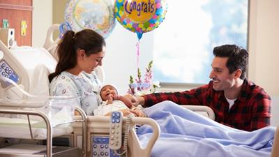 Mom and dad with new baby in hospital room