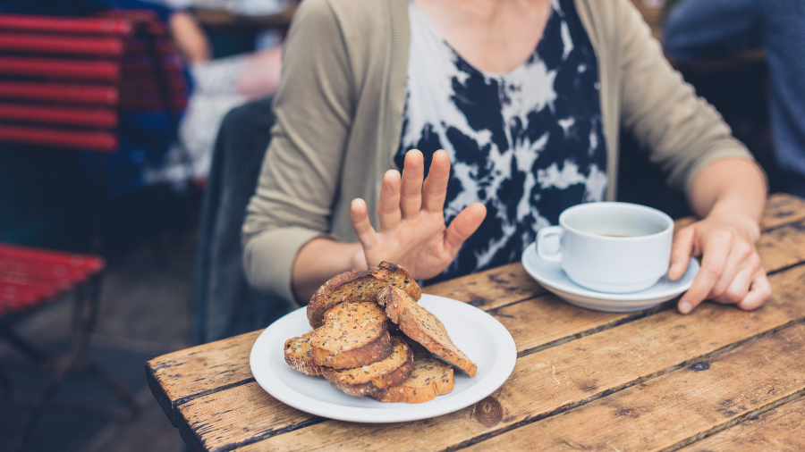 A woman refusing bread at a cafe due to a gluten intolerance