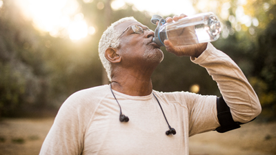 An older African American male drinking water outdoors after working out.