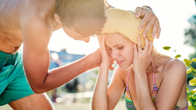 Young male caring for a young female experiencing heat stroke on the beach.