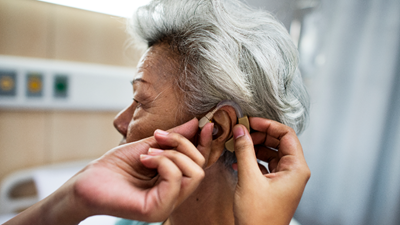 Physician placing hearing aid into the ear of an older woman.
