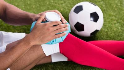soccer player applying ice to a knee injury.