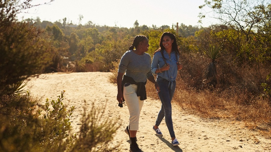 Two women staying healthy by going for a walk.