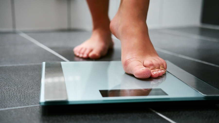 Obese person getting on scale
