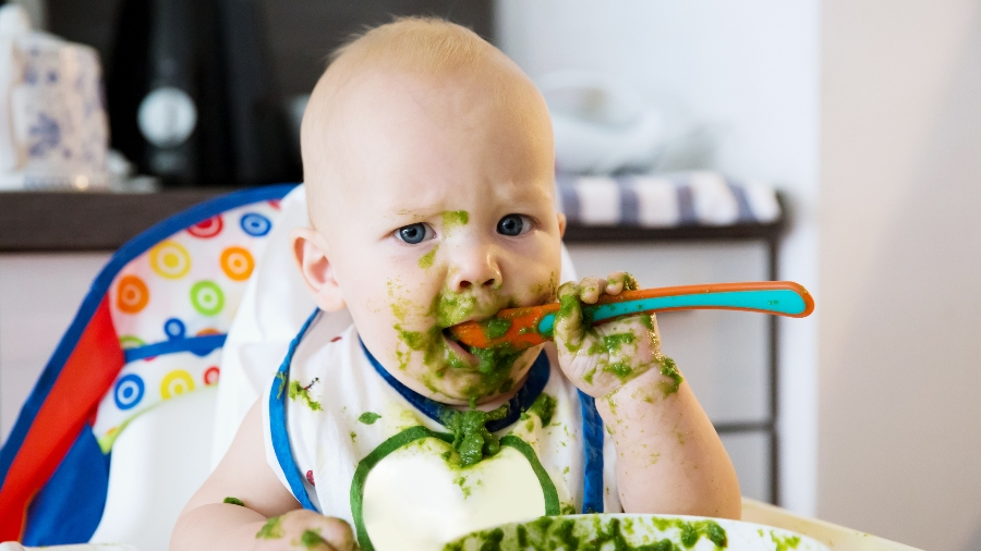 Baby eating green food