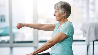 Elderly woman lifting small weights