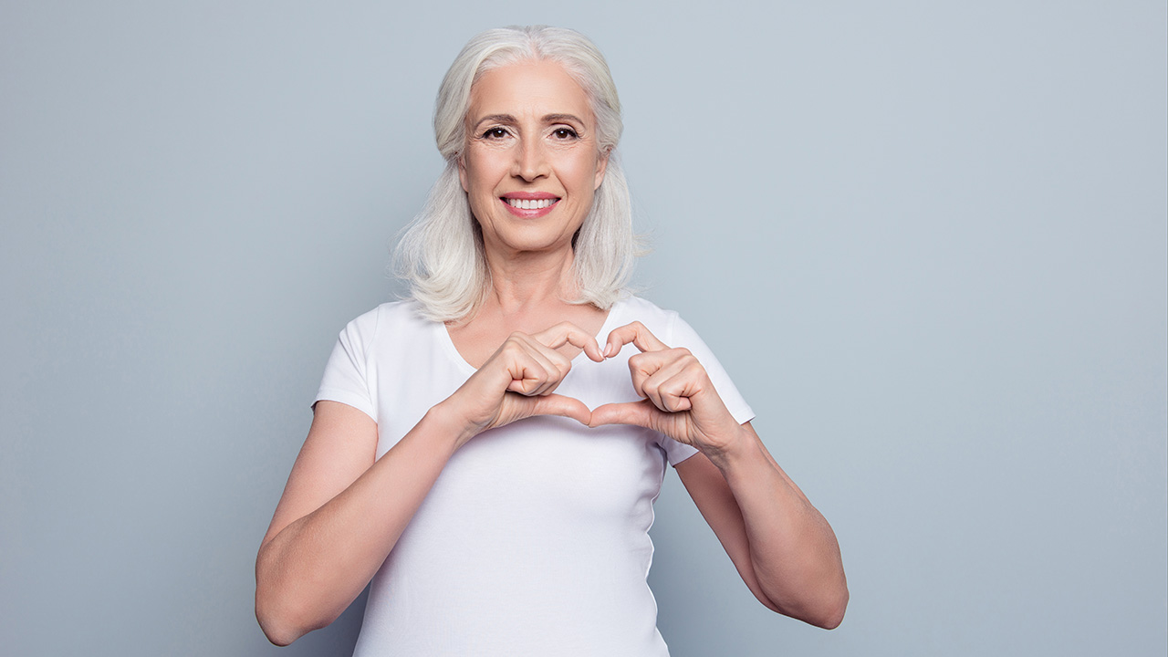 Female holding hands in shape of heart over chest