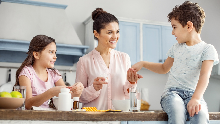 Mother giving children vitamins in kitchen