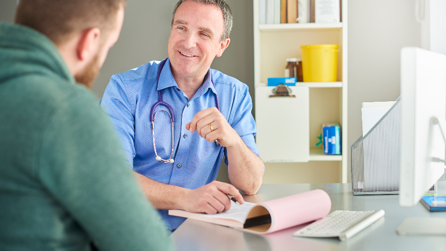 Gentleman talking to doctor about symptoms and treatment options for testicular cancer.