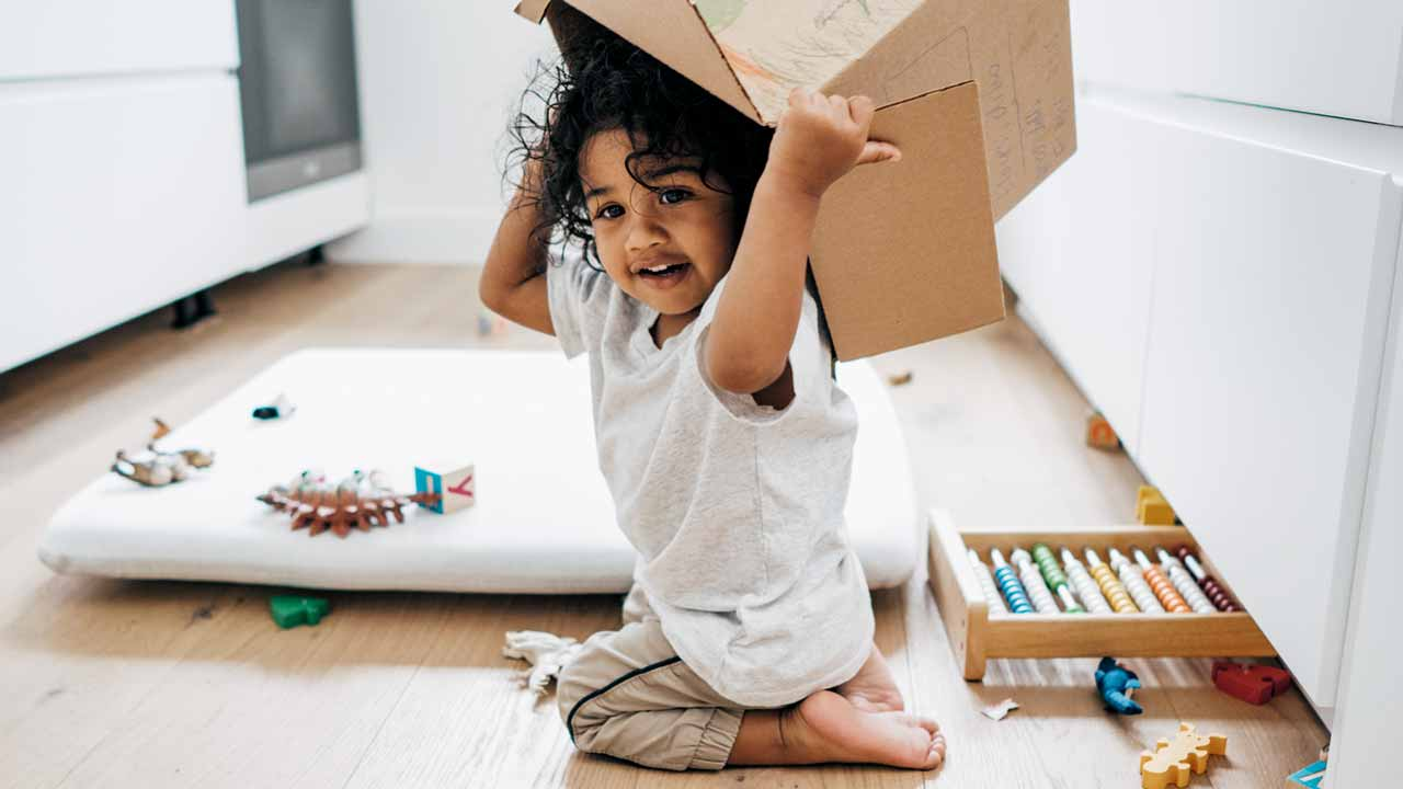 Preschooler holding toy box overhead surrounded by toys on floor