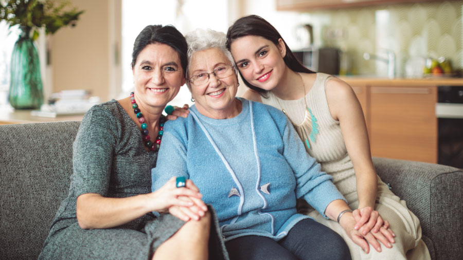 Three different generations of women sitting together and smiling