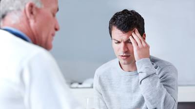 Male patient explaining headache to physician.