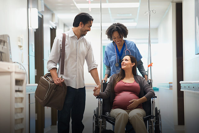 Pregnant woman and husband being walked to delivery room