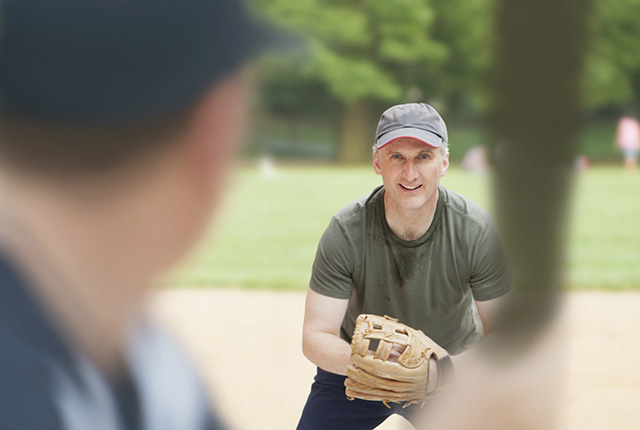 Pitcher about to throw baseball to child batter