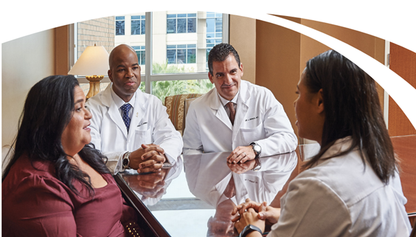 Team of physicians sitting with patient around a table discussing lung cancer diagnosis.