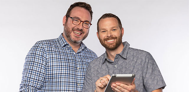Male couple smiling holding tablet