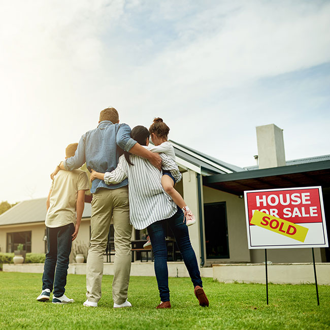 Family hugging outside of sold house