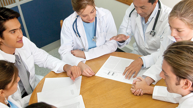 Doctors talking around conference table