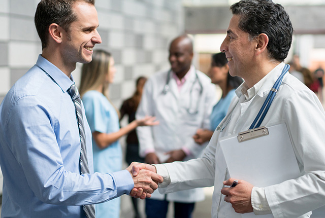 Insurance salesman and physician shaking hands