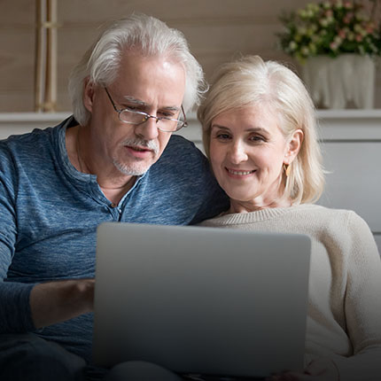 Mature couple looking on laptop