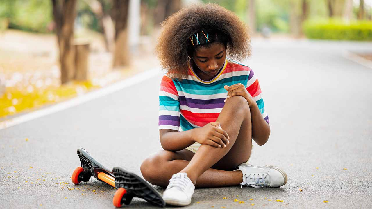 Young girl assessing her knee sprain after falling off of skateboard