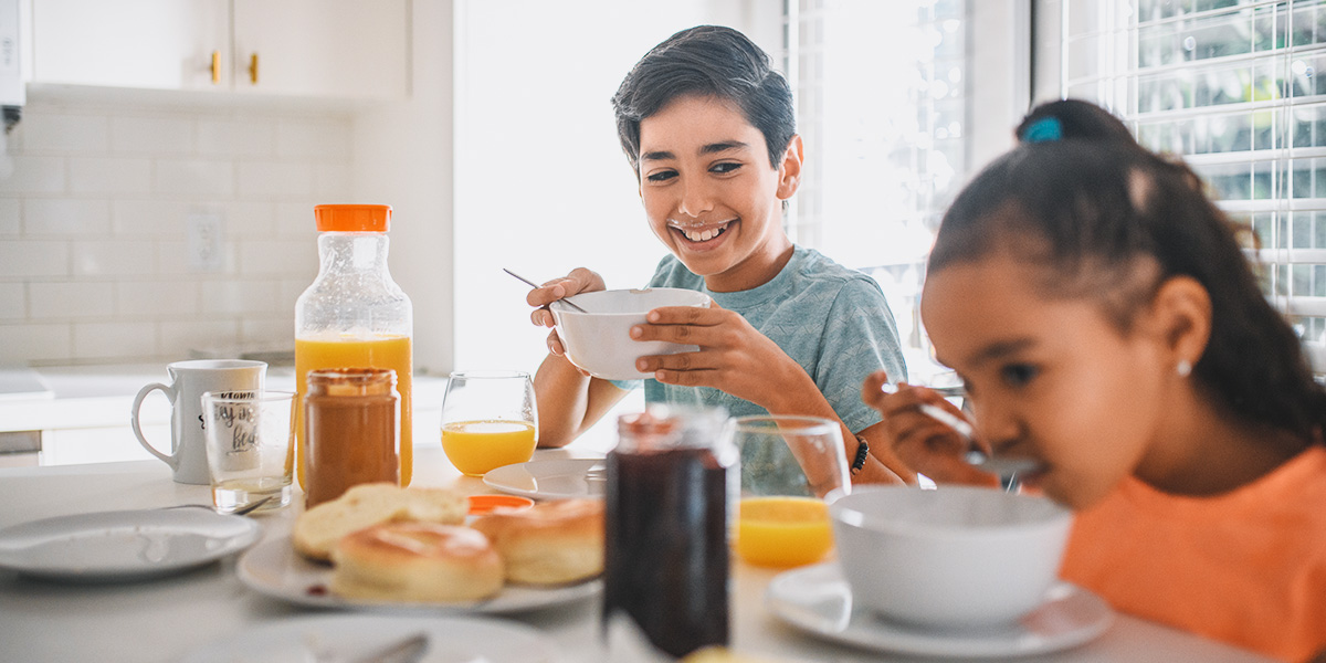 Siblings eating breakfast at their kitchen table